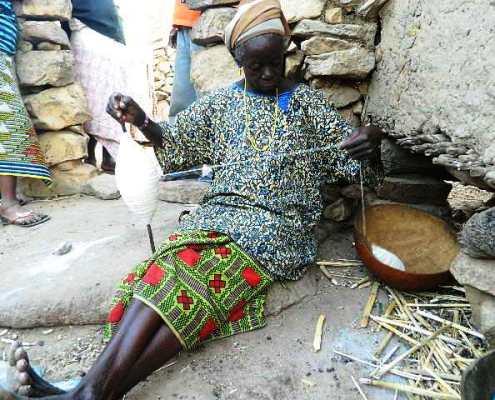 Elle file le coton au village.